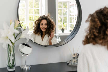 Natural beauty and haircare concept. Charming african american woman in bathrobe looking at mirror in bathroom, touching fresh healthy hair and smiling wide after spa procedure at home