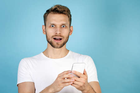 Portrait of wondered and excited adult guy in white t-shirt using modern smartphone, making steering eyes, open mouth while he standing isolated on blue copy space background