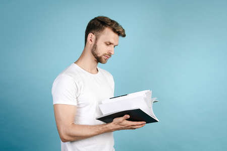 Side view of confident, young adult and smart student guy reading science magazine, standing isolated on blue copy space background in white t-shirt. Education concept