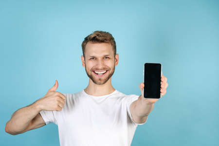 Advertising concept. Happy and smiling young guy in casual white t-shirt showing thumbs up, holding modern smartphone with blank screen display, standing isolated on blue copy space background