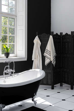 Vertical photo of modern interior design in contemporary bathroom with classic bath, decorative dressing screen, towels and bathrobe for daily morning routine and beauty procedure in spa salon