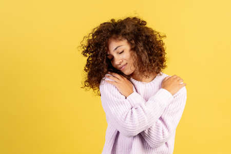 Love concept. Smiling, lovely young african american woman hug and care herself, standing on yellow copy space background with closed eyes and dreamy face