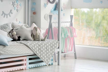 Element of childrens bedroom with plaid, pillows and toys on comfort bed, house decor, clothes on rack near window in modern apartment interior with copy space