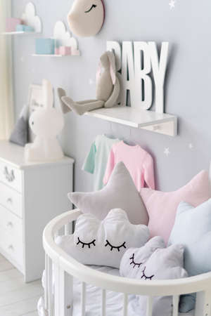 Vertical view of bedroom for newborn child with pillows in cradle bed, white wooden commode, toys and house decor on blurred background in apartment with scandinavian interior design 版權商用圖片