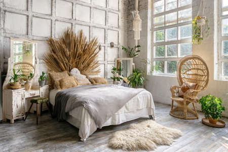 Side view of authentic cozy bedroom with interior design in boho chic style, decorative headboard over comfort bed, wicker armchair, houseplants near commode and mirror. Lovely room in classic house