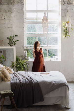 Vertical view of dreamy young woman standing near window at cozy bedroom with interior design in boho chic style. Female enjoying early weekend morning