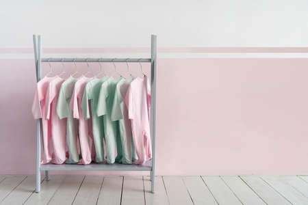 Colorful cotton wear for toddlers on rack hanger in shop against pastel pink background with copy space. Concept of apparel for kids
