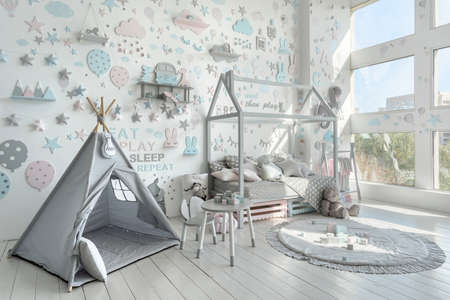 Childrens bedroom with tent, pillows on comfort bed, toys and house decor in play room with nordic interior style. Happy childhood concept