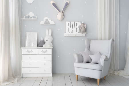 Kids playroom with white wooden commode, bunny toys, picture frame, star pillows on comfort armchair and house decor, in light minimalist apartment interior
