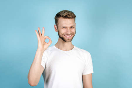 Happy young adult student guy making okay sign, smiling nice and standing isolated on blue copy space background in white t-shirt. Concept of recommend and advertise