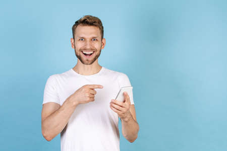 Concept on new online app. Happy and excited adult man pointing with finger on modern smartphone, standing isolated on blue copy space background, wearing in white t-shirt