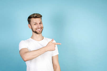 Happy and smiling young man in white t-shirt pointing with finger aside, looking at camera, recommend news, standing isolated on blue copy space background. Sale and discount advertise