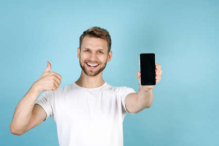 Confident young adult guy making advertising of smartphone. Man showing thumbs up, holding modern cell phone with blank screen display, standing isolated on blue copy space background in white t-shirt