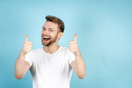 Good news everyone. Portrait of adult student guy showing thumbs up on both hands, making happy, smiling face and standing isolated on blue copy space background in white t-shirt 版權商用圖片 - 156884360