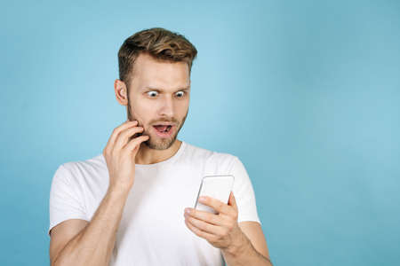 Shocked young guy looking at modern smartphone display, making excited face, standing isolated on blue copy space background in white t-shirt. Concept of sale and discount in online store 版權商用圖片
