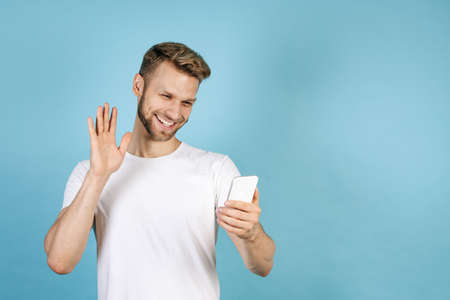 Social distancing concept. Happy young adult guy making video call on modern smartphone, waving hands, smiling wide, standing isolated on blue copy space background in white t-shirt