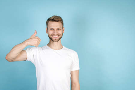 Good deal concept. Successful and confident adult man in white t-shirt showing thumb up, smiling wide, looking at camera, standing isolated on blue copy space background