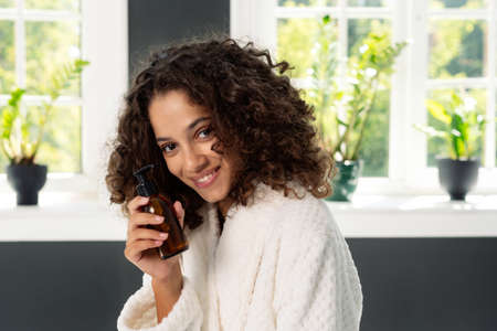 Concept of beauty procedure. Portrait of young african american woman smiling wide, holding skincare cosmetic product in hands, standing in bathrobe at bathroom 版權商用圖片 - 156884450