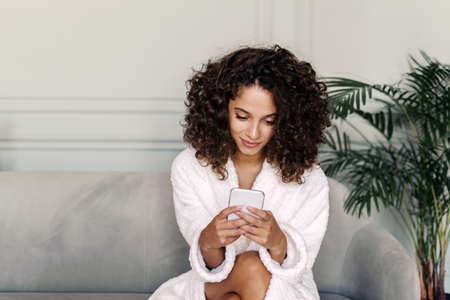 Portrait of smiling young adult african american woman in bathrobe using modern smartphone, spending weekend at home, sitting in living room, texting message and reading online news blog