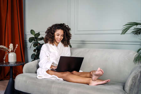 Concept of weekend at home. Full length view of happy african american woman in bathrobe sitting on couch in living room, using modern laptop computer, resting at home, spending free time in internet
