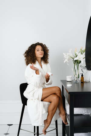 Skincare and bodycare concept. Vertical full length view of afro american woman holding container with moisturizing cream in hands, after skin care procedure, sitting in bathrobe, looking on camera