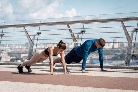 Workout and healthy lifestyle concept. Side view of young athletic woman and man doing push ups exercise, standing in plank pose, making sport training outdoors together