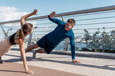 Concept of fitness activity in city. Two happy young adult sporty friends making high five gesture after sport training outdoors, standing in plank pose together, support each other