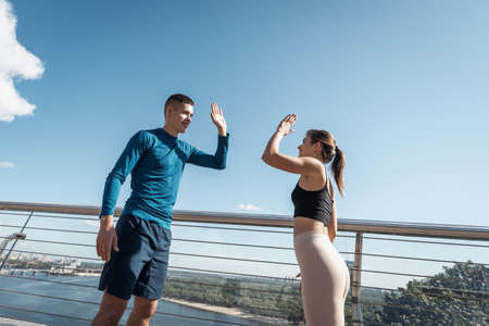 Morning exercise and workout concept. Low angle view of two happy young friends give five after sport training outdoors, standing against copy space sky together 版權商用圖片 - 156884746