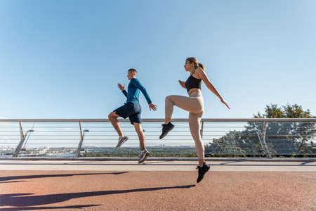 Concept of healthy lifestyle. Low angle and side view of young adult woman and active man making sport training outdoors together, jumping high in city