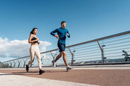 Morning workout concept. Low angle view of fast adult athlete woman and man running together in city, making sport training outdoors