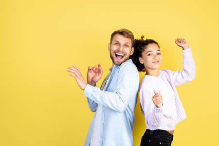 Party and celebration concept. Happy interracial couple dancing together, smiling wide, standing back to back on yellow copy space background 写真素材
