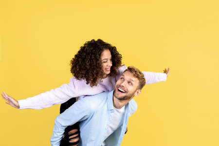 Happy adult man carry smiling african american woman while she making airplane gestures. Two friends having fun, standing isolated on yellow copy space background