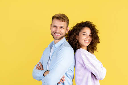 Adult man standing back to back with african american woman against yellow copy space background. Happy confident people smiling wide, crossed hands over chest, looking at camera