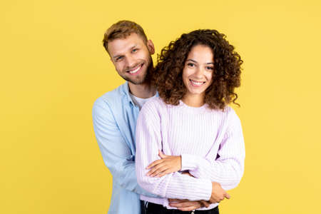 Love and relationship concept. Happy mixed race couple hugging, smiling wide and looking at camera, standing together isolated on yellow copy space background 写真素材