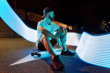 Sport and nightlife concept. Young adult handsome man sitting on skateboard at street with neon light, looking aside, resting after night ride in urban city 写真素材