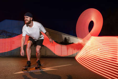 Sporty and happy man riding on skateboard at street with neon light. Smiling youth guy standing on board against fluorescent urban illuminations