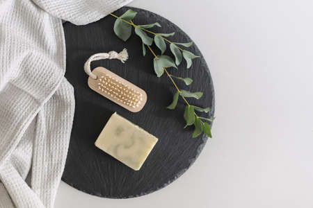 Concept of recycle, reduce, reuse. Flat lay, top view of wooden nail brush and organic handmade soap near towel with eucalyptus plant on black plate stand against white copy space background