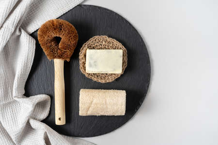 Concept of sustainable life. Flat lay, top view of coconut brush with wooden handle and solid organic detergent soap on black plate near kitchen towel against white copy space background 写真素材