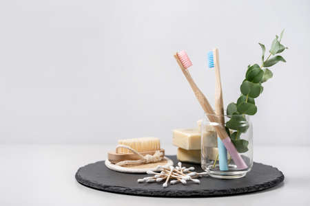 Zero waste concept. Bamboo toothbrush in cup, nail brush, organic solid soap, wooden ear sticks and all bathroom supplies with eucalyptus plant on black plate stand against white copy space background 写真素材
