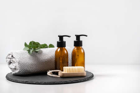 Concept natural and organic cosmetic. Zero waste nail brush, glass dispenser bottle with shower gel, shampoo, soan and eucalyptus plant on black plate stand against white copy space background 写真素材