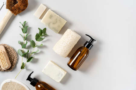 Concept of nature care and eco friendly items. Flat lay, top view of solid handmade soap, luffa sponge, coconut brush, glass dispenser bottle near eucalyptus plant on white copy space background
