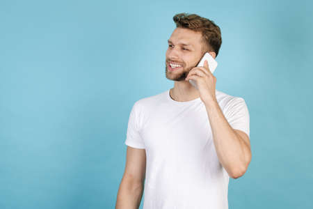 Side view of smiling adult man in white t-shirt looking aside, talking on modern smartphone and standing isolated on blue copy space background. Communication concept