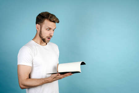 Successful exam concept. Side view of young man in white t-shirt making shocked face, looking at copybook with homework, standing isolated on blue copy space background