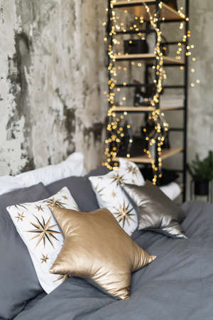 Selective focus on star shaped pillows at comfortable bed. Vertical view of bedroom in modern design apartment with cozy stuff against blurred rack on background