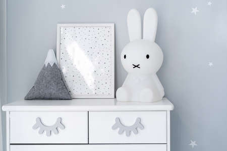 Close up view of bunny toy and picture frame on white wooden dresser against light wall on background. Decor in childrens room with modern interior design