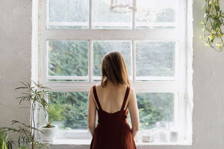 Beautiful adult woman standing near large window, looking at view, spending time in white room with interior design in loft style. Female resting at home, enjoying early morning at weekend 版權商用圖片