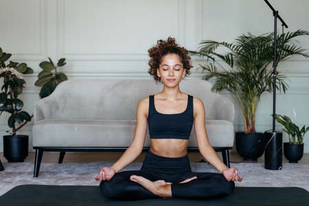 Mental health concept. Peaceful sportive afro american woman meditates on yoga mat, training at home, making sport exercise and zen practice with nice smile