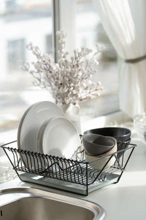 Vertical view of plates, clean dishes, kitchenware utensil on metal dryer rack against blurred bouquet in white vase in cozy home at modern kitchen