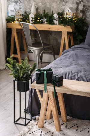 Vertical view of two gift box on wooden bench near comfort bed in cozy bedroom with modern interior design, winter decorations and fir in flower pot 版權商用圖片