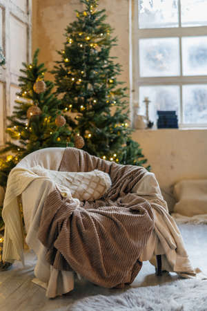 Cozy living room in winter style interior, comfort armchair against background with decorated new year tree, garland lights and traditional decor at home